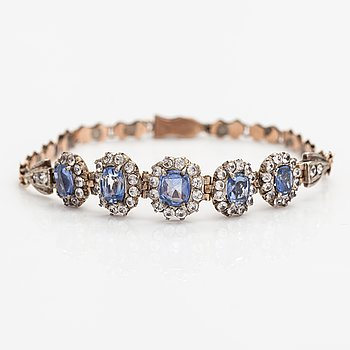 A gold bracelet with light blue and white sapphires.