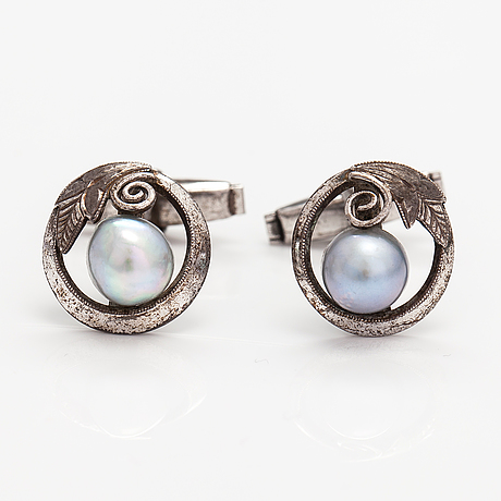 A pair of silver cufflinks with cultured baroque/akoya pearls.