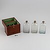 A late empire mahogany box with three glass bottles, mid 19th century.