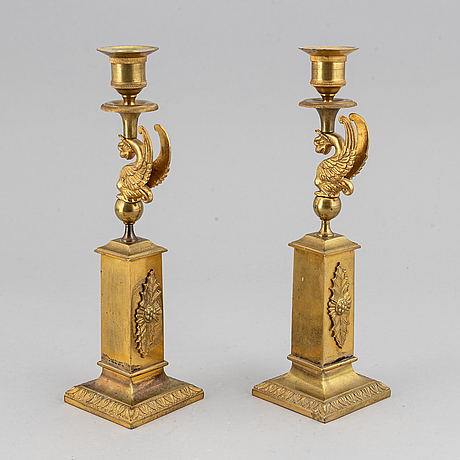 A pair of early 20th century brass empire style candlesticks.