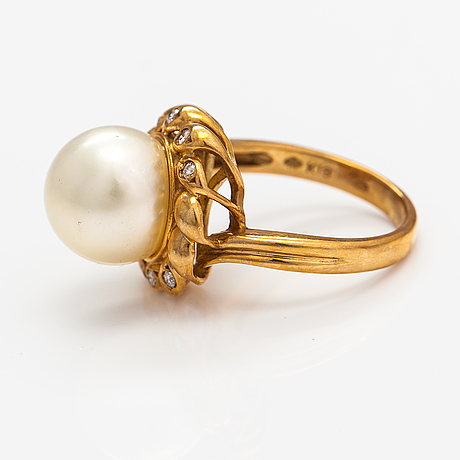 An 18k gold ring with a cultured pearl and dimaonds ca. 0.09 ct according to engraving.