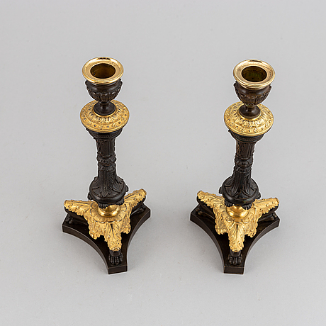 A pair of late empirepartially gilded bronze candlesticks, mid 19th century.