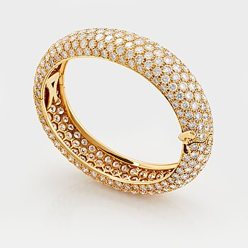 894. Cartier an 18K gold bangle set with round brilliant-cut diamonds.