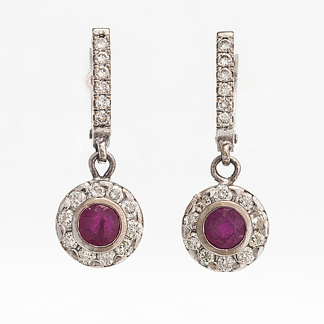 A pair of 14k white gold earrings with lead glass treated rubies and diamonds ca. 1.20 ct in total.