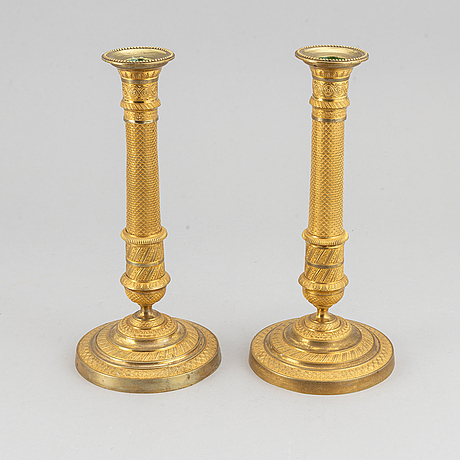 An early 19th century pair of bronze empire candle sticks.
