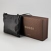 Gucci, a leather messenger bag.