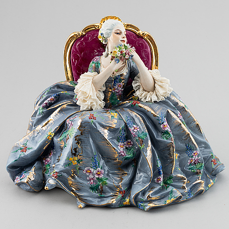 A porcelain figurine of a seated rococo lady, 20th century, italy.
