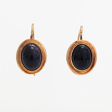 A pair of 14k ogld earrings with purplr goldstones. turku.