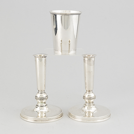 A swedish silver beaker and a pair of candlesticks.