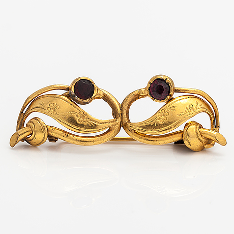 A 14-18k gold brooch with one garnet and one glass stone.