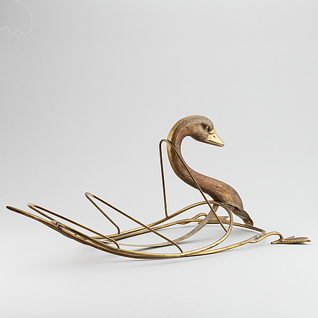 A 20th century grass newspaper stand in the shape of a swan.