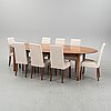 An stained oak dining table with eight chairs.