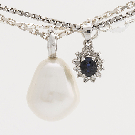 2 pendants 18k whitegold with 1 cultured pearl approx 13,5 mm and 1 sapphire approx 4x3 mm and diamonds, 5 silver chains.
