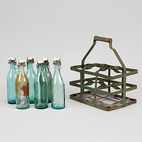 A 19th century tinplate bottle stand with six glass bottles.