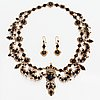 A 14k gold necklace with onyx and garnets.