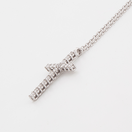 Brilliant-cut diamond cross pendant.
