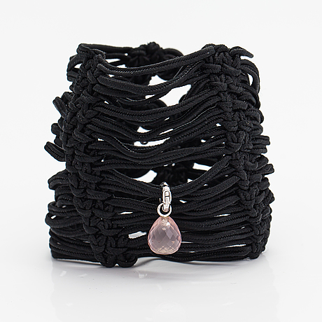 """Ole lynggaard, a satin like band bracelet with an 18k white gold and rose quartz """"sweet drops"""" pendant."""
