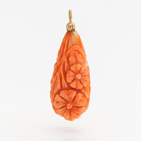 A pendant with carved coral and gold.