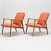 A pair of 1950s upholstered armchairs with wood armrests.