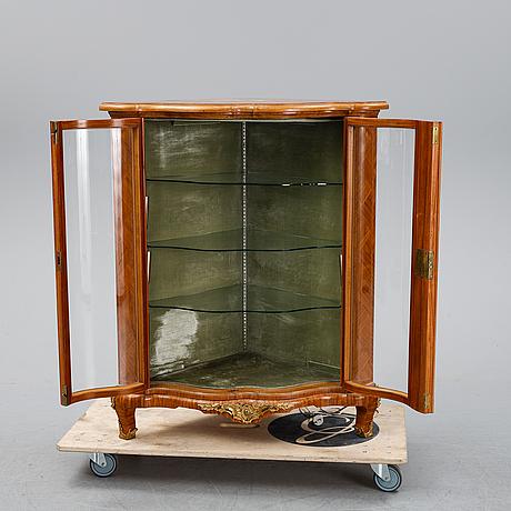 A 20th century rococo style corner cabinet.