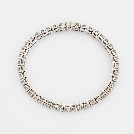 A tennis bracelet in 18k gold set with round brilliant-cut diamonds.