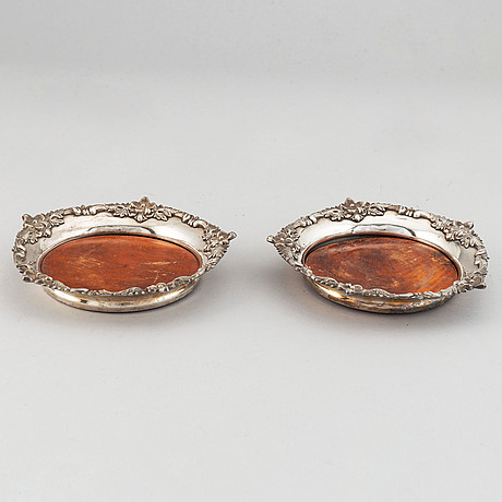 A pair of silver plate and wood coasters, circa 1900.
