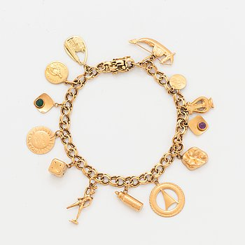 An 18 gold bracelet with 13 charms.
