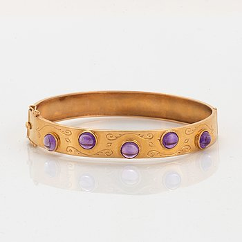An 18K gold bangle set with amethysts.