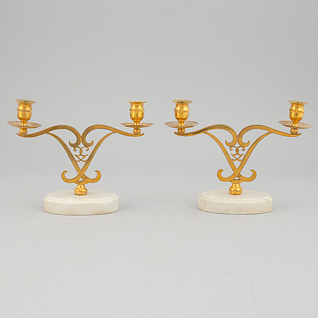 A pair of brass candle sticks om marble stands from the middle of 20th century.