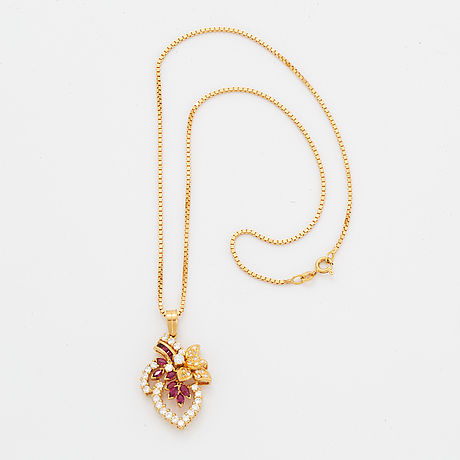 An 18k gold pendant set with faceted rubies.