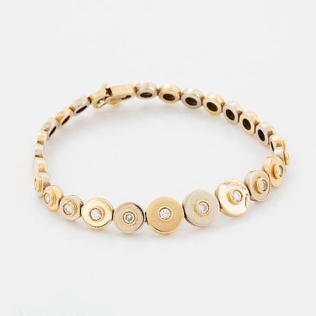 A 14k gold bracelet set with round brilliant-cut diamonds.