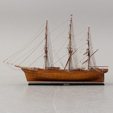 A wooden scale model of cutty sark on a painted wooden stand.