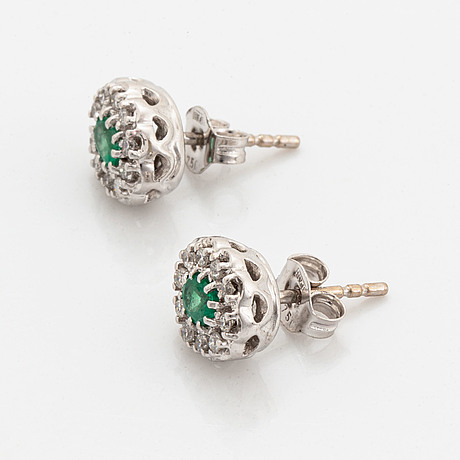 A pair of 18k gold earrings set with faceted emeralds.