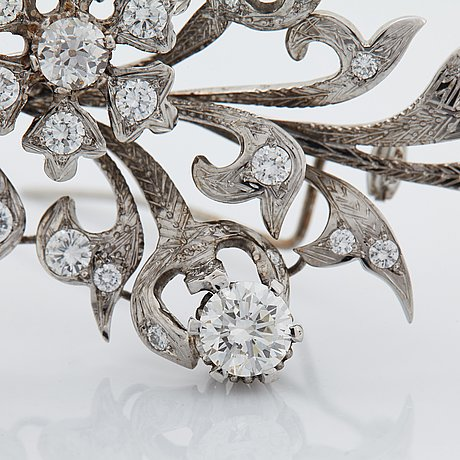An 18k white gold brooch set with round brilliant-cut diamonds.