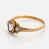 An 18k gold ring set with an amethyst and two pearls.