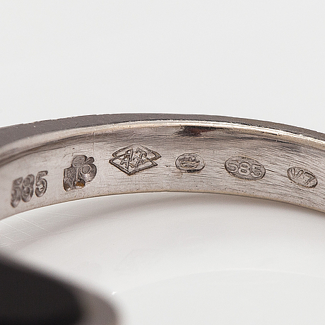 A 14k white gold ring with diamonds ca. 0.06 in total and onyxes. import marked tillander, helsinki 1974.