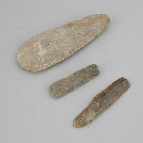A neolithic axe and two flint tools.