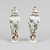 A pair of famille rose vases with covers, qing dynasty, 18th century.