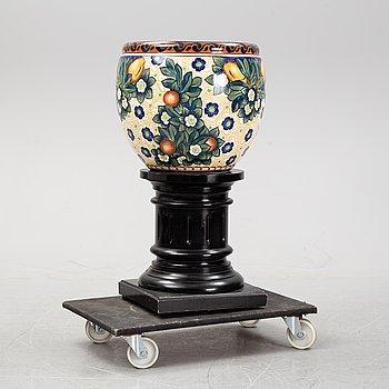 A handpainted faience, urn on wooden pedestal. Alumina, Denmark. Dated 1910.