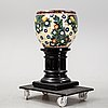 A handpainted faience, urn on wooden pedestal. aluminia, denmark. dated 1910.