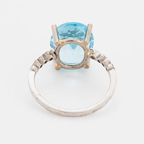 Oval faceted blue topaz and brilliant-cut diamond cocktail ring.