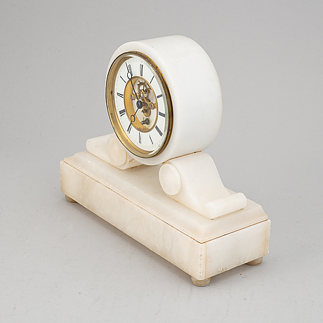 An alabaster mantle clock and pair of candlesticks, circa 1900.