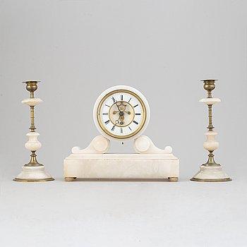 An alabaster mantle clock and pair of candlesticks, circa 1900.