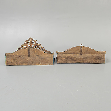 Two painted and carved wooden clothes hangers, indonesia, 20th century.