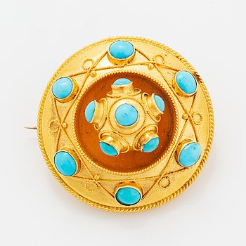 A cabochon-cut turquoise, 14K gold brooch.