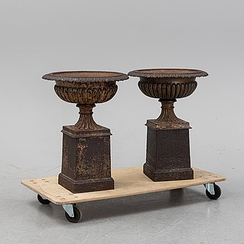 A pair of cast iron urns and stands, 20th Century.