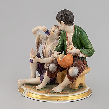 A porcelain figurin of two ragged boys eating watermelon, Rudolstadt Volkstedt, Germany, ealr 20th century.