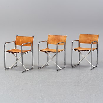 Three leather upholstered folding chairs.