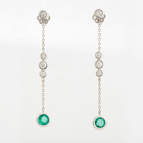 A pair of 18k white gold earrings set with faceted emeralds.
