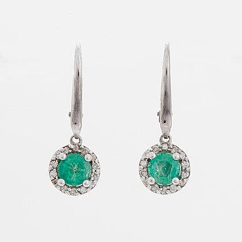 Ett par smaragdörhängen med briljantslipade diamanter.